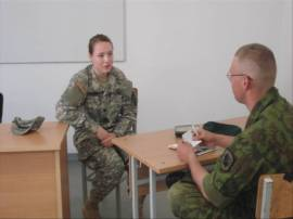 Me teaching a Lithuanian soldier English terms and how to formulate sentences using those terms.